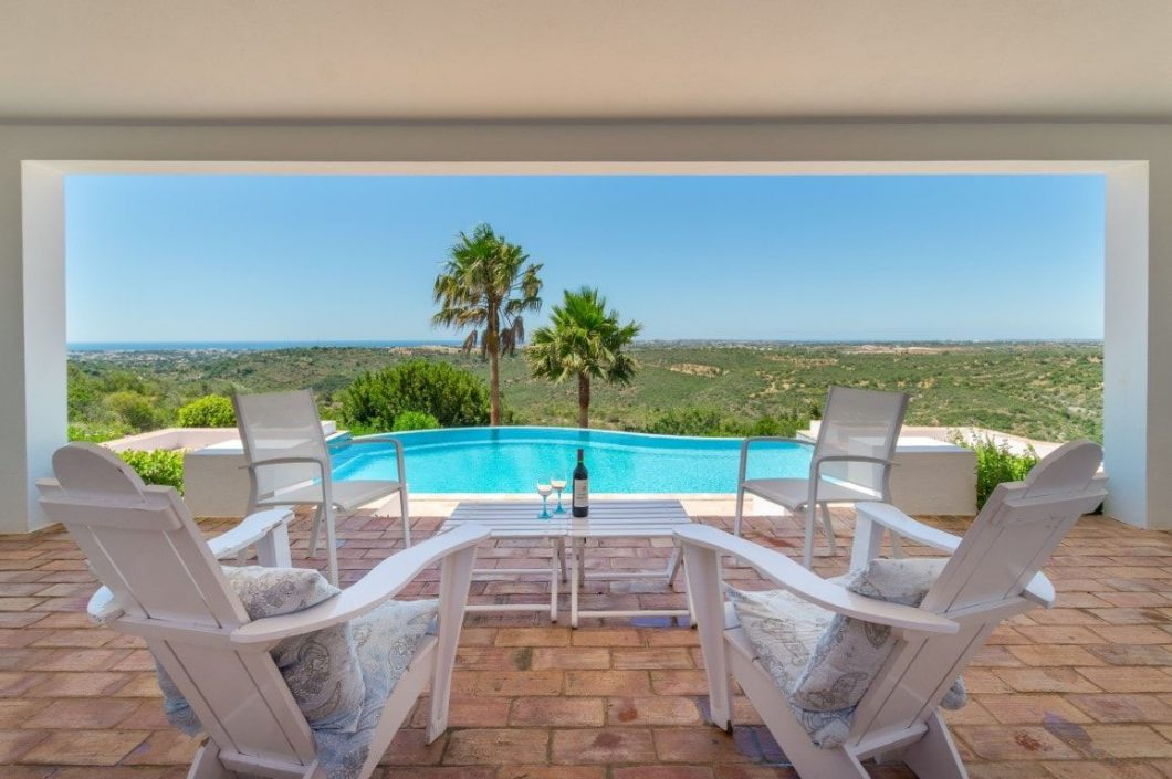 four chairs and table by the pool overlooking an amazing landscape
